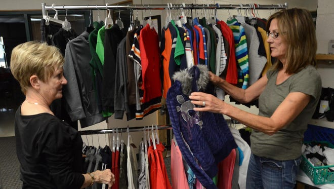 """Community Sharing's Barb Maher, (left, checking out donated clothes wth Karen Romanski) is being remembered as a """"sparkling light."""""""