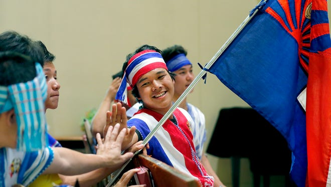 Originally borne in Thailand, Aye Wathy Myat,17, high-fives friends next to the Karen flag during a World Refugee Day celebration at Lake Avenue Baptist Church. The Karen people are the third largest ethnic group in Burma.