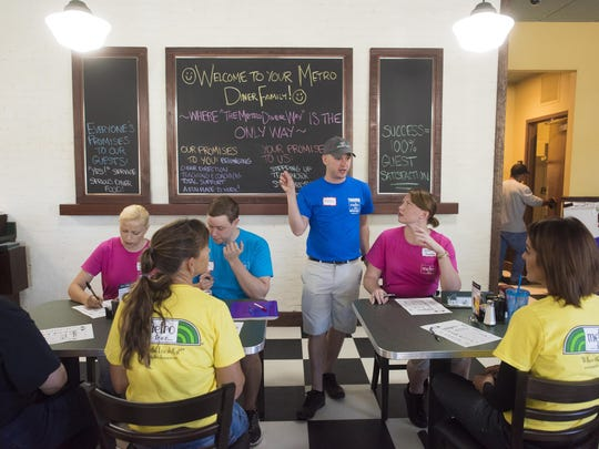 Matthew Hawking, center, a server trainer, goes over a floor plan with wait staff members during training at Metro Diner in North Naples last week.