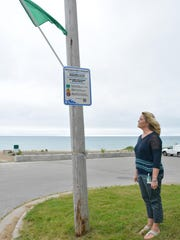 Cynthia Kinnard, Kewaunee County Public Health Nurse, examines one of the new flags at Selner Park beach that advises swimmers of beach conditions.