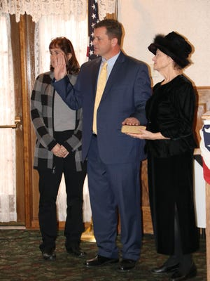 Mayor Kelly Decker takes the oath of office accompanied by his wife, Jill, and his mother, Carol Decker. In his speech, he enumerated signs of progress in Port Jervis.