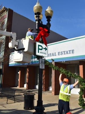 City crews put up holiday lights in downtown Coldwater.