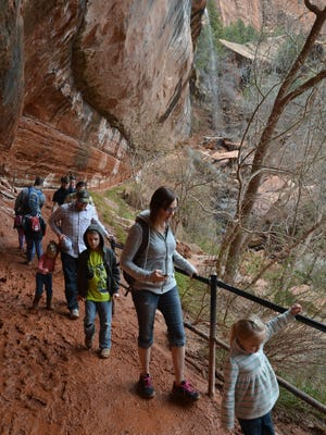 Families work their way through muddy sections of the Emerald Pools trail in Zion National Park. The advantages of visiting the park in the off-season include cooler temps ideal for all day hiking excursions and less foot traffic.