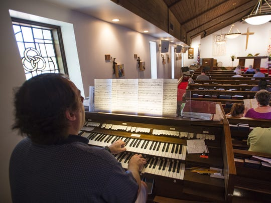 Monty Hogan plays the organ before a service at St. Paul's Episcopal Church on W. Elizabeth Street on Sunday. The church property has been sold to make way for a student housing development.