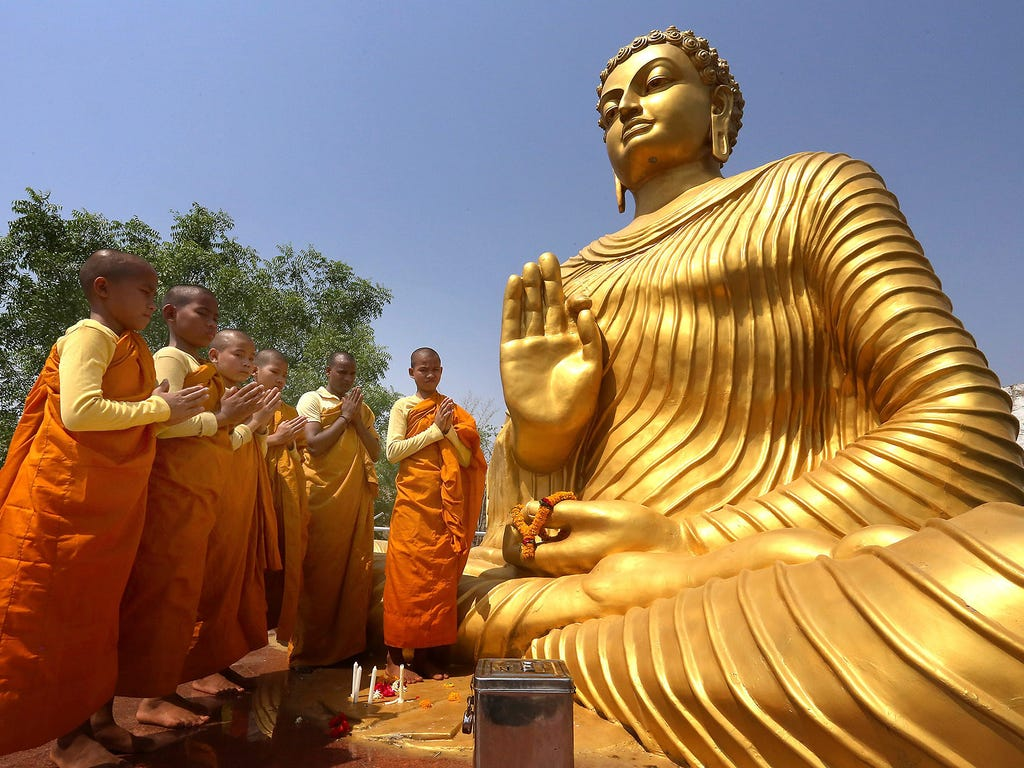 Monks pray in front of a statue of Buddha during a religious celebration on May 4 in Bhopal, India.