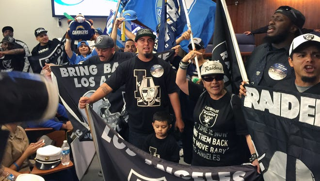 """In this photo taken Tuesday, April 21, 2015, football fans, who want to see an NFL team return to the Los Angeles area after two decades, chant """" bring them back!"""" before a Carson City Council vote on whether to approve the plan to build an NFL football stadium for the Chargers and Raiders in Carson, Calif. A second City Council has approved a second proposed pro football stadium in the Los Angeles area, putting local issues to rest in the NFL's return to the region and leaving the next move to the teams that would seek to relocate and the league that must give its approval."""