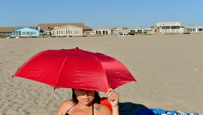 Rachel Ruiz of Oxnard peers out at the surf at Mandalay Beach in Oxnard in this file photo. The homes in the beachfront zone of the city are popular among visitors. More than a dozen of them are used for vacation rentals.