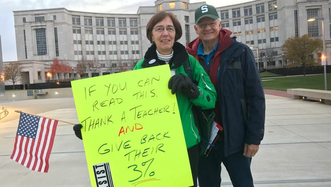 Mary Jo Hardy of Okemos and her husband Bruce Alexander demonstrate outside the Michigan Supreme Court Hall of Justice Tuesday, Nov. 7, 2017 on the eve of oral arguments in a long-running school employee retirement case.