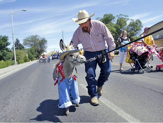 David Meador, of Bloomfield, walks with Tater, a 2-month=old miniature donkey, during the Olde Tyme Family Fourth parade in Bloomfield on the Fourth of July 2014.