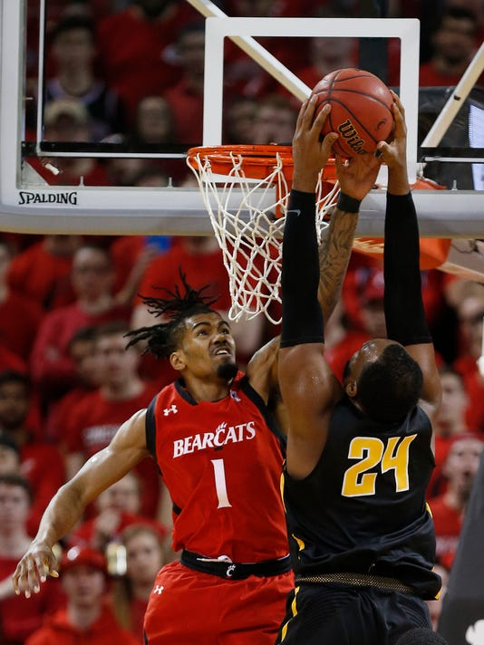 Wichita State center Shaquille Morris (24) goes to the basket over Cincinnati guard Jacob Evans (1) during the first half of an NCAA college basketball game, Sunday, Feb. 18, 2018, in Highland Heights, Ky. (AP Photo/Gary Landers)