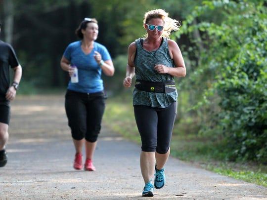 Shawn Fadoir, front, runs on The Oaks Trail as she prepares to run the Gateway 10K in August.