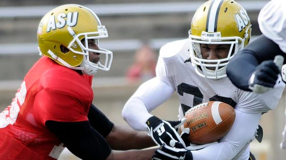 Alabama State quarterback Daniel Duhart hands off to running back Malcolm Cyrus during a team scrimmage on Saturday, March 15, 2014.