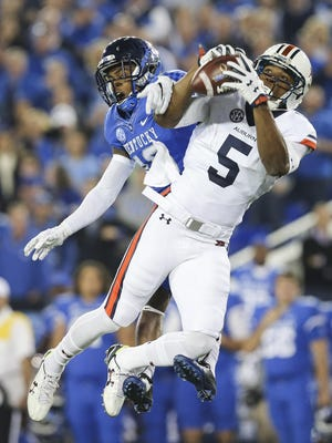 Auburn wide receiver Ricardo Louis catches a pass in front of Kentucky cornerback Cody Quinn.