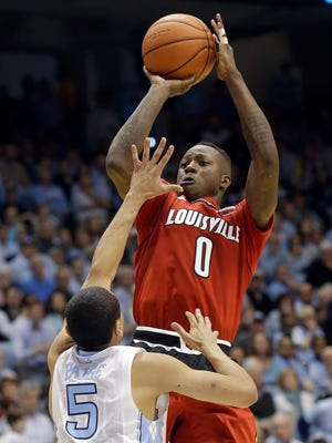 North Carolina's Marcus Paige (5) defends as Louisville's Terry Rozier (0) shoots during the second half of an NCAA college basketball game in Chapel Hill, N.C., Saturday, Jan. 10, 2015. North Carolina won 72-71. (AP Photo/Gerry Broome)