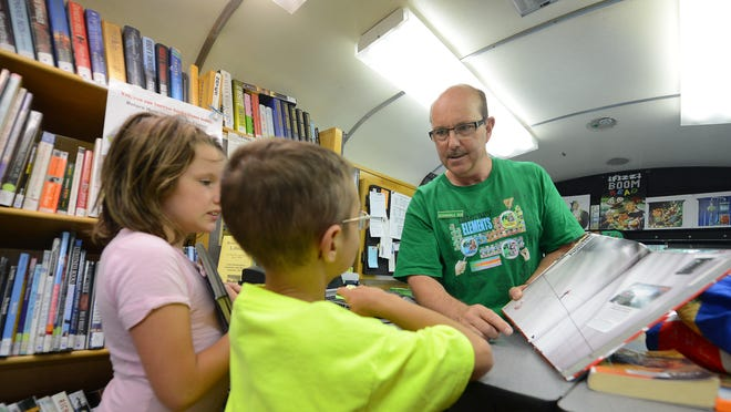 Bob Ripley, right, known as Bookmobile Bob, discusses a book choice with Bobby and Brianna Haase inside the Brown County Bookmobile on Tuesday.