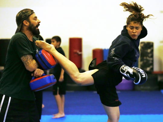 Cynthia Arceo delivers a kick to pads held by Shane Schuman during a workout. Arceo, prekindergarten aide, is preparing for an upcoming MMA bout Oct. 31.