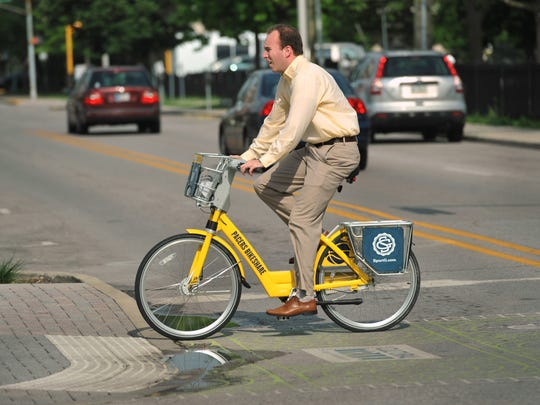 A rider heads up Alabama Street on a Pacers Bikeshare bicycle Monday June 30, 2014.
