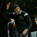 FILE - In this Oct. 28, 2014, file photo, San Antonio Spurs' Tim Duncan, left, holds up his 2014 NBA championship ring during a ceremony prior to an NBA basketball game between the Spurs and the Dallas Mavericks, in San Antonio. Duncan announced his retirement on Monday, July 11, 2016, after 19 seasons, five championships, two MVP awards and 15 All-Star appearances. It marks the end of an era for the Spurs and the NBA.