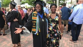 FGCU grad Evelyn Philistin, 22, and her mother Clarisia Marc, after the university's spring commencement Sunday.