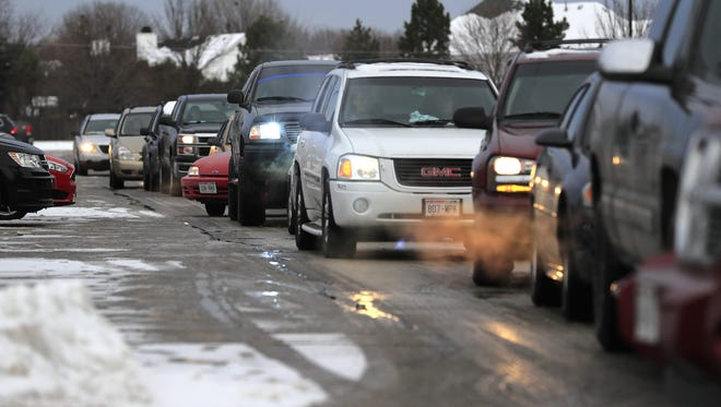 Students drive out of the parking lot at the end of the school day at De Pere High School on Wednesday, Dec. 21, 2016. Students who have parking permits at the school are subjected to random drug testing throughout the school year.