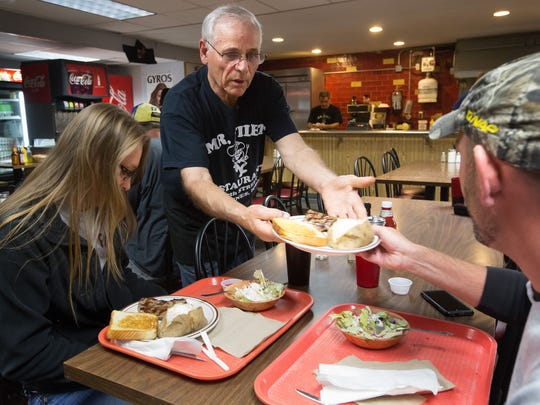 George Hatzigiannakis, owner of Mr. Filet Steakhouse, delivers a steak with fixings to a table Tuesday.