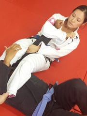 Hannah Cho Iriarte practices an arm bar on her teammate Kean Sucgang while sparring in Brazilian jiujitsu.