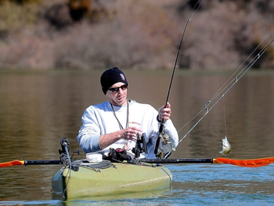 Matt Steyer of Stewartstown pulls a fish from the water while fishing from a kayak on Lake Redman. A good fisherman doesn't need expensive equipment.