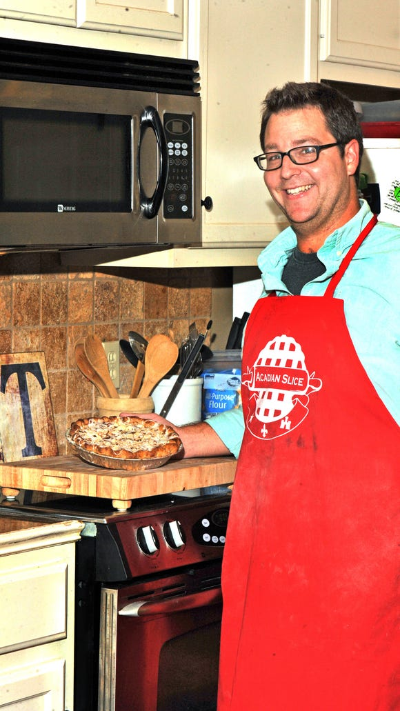 Korey Champagne, owner of Acadian Slice Bakery, displays a cherry pie