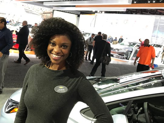 Chevrolet product specialist Lauryn, standing next to a 2018 Chevrolet Cruze, sports a gray sweater dress.