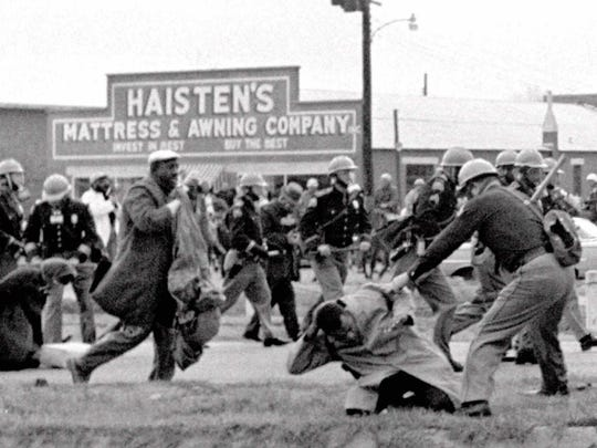 This file photo shows Alabama State troopers swinging billy clubs to break up a civil rights voting march in Selma, Ala., March 7, 1965.