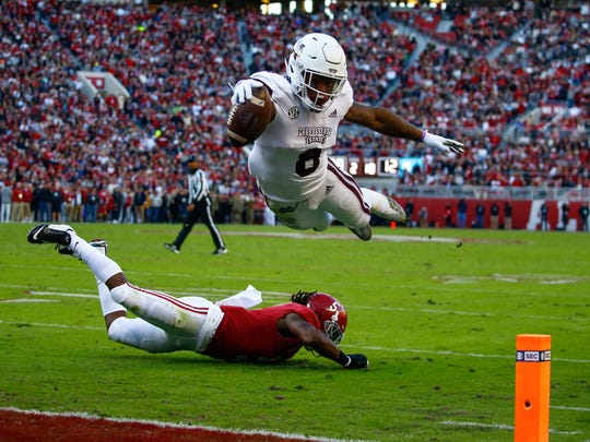 Mississippi State running back Kylin Hill (8) dives over Alabama defensive back Shyheim Carter (5) for the end zone, but the play was called back for a penalty during the first half of an NCAA college football game, Saturday, Nov. 10, 2018, in Tuscaloosa, Ala. (AP Photo/Butch Dill)