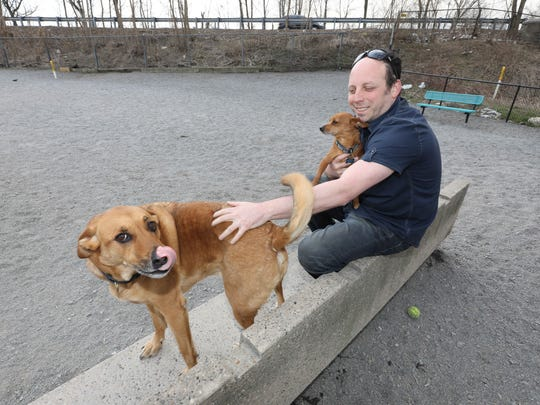 Ken Wile plays with his dogs, Freddy, left and Theo,