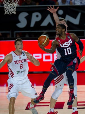 United States's Kyrie Irving, right, goes for the basket in front Turkey's Baris Hersek, left, during the Group C Basketball World Cup match, in Bilbao northern Spain, Sunday, Aug. 31, 2014. The 2014 Basketball World Cup competition take place in various cities in Spain from  last Aug. 30 through to Sept. 14.