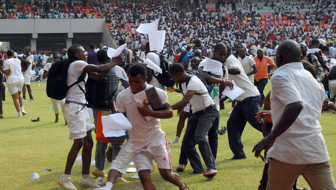 Job-seekers applying for work at the Nigerian immigration department scramble as their exam papers fly in the air, on the pitch of Abuja National Stadium.