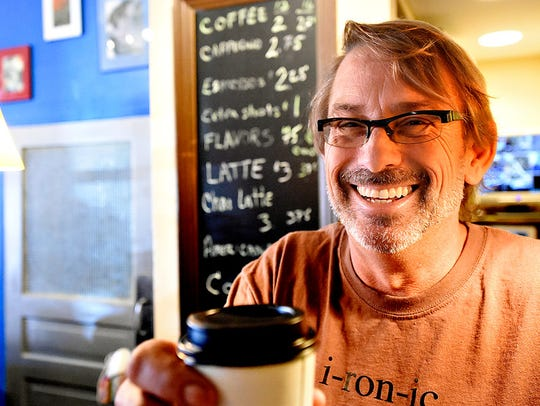 Co-owner David Smith , of  i-ron-ic, serves up a latte