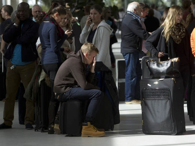Philipp Schwab, a resident of Frankfurt Germany with a home in Cape Coral waits in line at the Delta Airlines ticket counter at Southwest Florida International Airport with his girlfriend, Jana Becher, center left. Their flight to New York was cancelled Friday due to bad weather in the Northeast.  They were in line to rewrite their tickets. Numerous flights from Southwest Florida to the Northeast were either delayed or cancelled due to the weather.