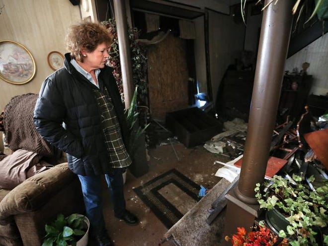 Leigh McCall looks over her living room that was destroyed by a car that flew into her house (in background) at the intersections of Warman Avenue and Jackson Streets Sunday, December 29, 2013. Leigh McCall and her husband Tim have lived in the home for the past 30 years and have had 11 accidents of cars into their home over that time span.