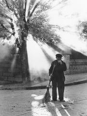 """The Street Sweeper,"" 1966.  ""As smoke from burning leaves filter through the trees, a street sweeper in Escorial, Spain, takes a moments break in his duties and one of the Senator's best known photographs is born."" -- as published in Random House's ""People and Places: Photographs by Barry Goldwater"""