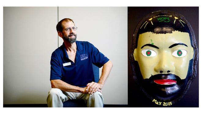 """Joe Barrett, 54, day program coordinator at Hinds' Feet FarmBrain injury caused by a bicycle accident in 2000Explanation of mask: Life is like a sport, you find what you're good at while growing up, then consistently hone those skills to increase efficiency with each passing year. The task(s) become automatic and the quality is satisfactory. There's reliability, a certainty that comes with each new day in one's profession, all is comfortable and progressing well. The unexpected traumatic brain injury, at age 39, became an all-stop action on my profession, and some cognitive abilities. This injury put me in a position to start over again. Though not from ground zero, it required me to open-up to a much greater degree than I had experienced before. I forced myself to go deeper within my heart to identify what was of interest post injury, and still within my capability level. What could I do with an acceptable level of competence in our culture that I would fully embrace?Helping others as a recreation therapist was revealed at the vocational rehabilitation screening. """"I can do this,"""" was my immediate feeling. I received help from many new friends as I headed on a journey to become a certified therapeutic recreation specialist. I use recreation as a tool to help individuals discover their current ability level and maximize their participation in any recreation activity of interest. My new journey came with many small failures, requiring me to adjust, adapt, and improvise as necessary to achieve acceptable standards on my new career path. The journey was worth it. Now it is 15 years post injury, and I'm working part time at Hinds' Feet Farm. I learned to let go of what no longer served the new me, and I accept my present level of human capacity, interests, and feelings about life's issues. I have found a comfort zone with myself and my team of supporters. Notice my mask and the color of my face. I admit, my ability to mix paints and generate the natural color"""