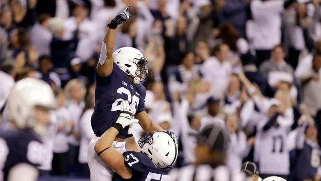 Penn State's Steven Gonzalez (57) lifts teammate Saquon Barkley (26) after Barkley scored on a 18-yard touchdown reception during the second half of the Big Ten championship NCAA college football game against Wisconsin, Saturday, Dec. 3, 2016, in Indianapolis. (AP Photo/Michael Conroy)