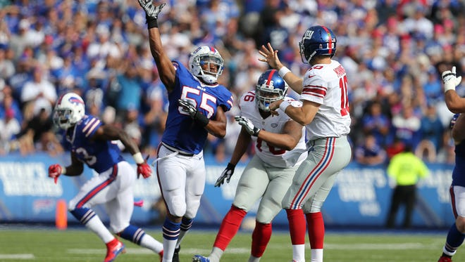 Giants quarterback Eli Manning dumps a short pass over Buffalo's Jerry Hughes that turned into a  51-yard scoring play to Rashad Jennings to help seal a 24-10 win.