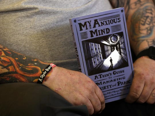 The tattooed arms of Tim Rogers, father of suicide victim Skyler Rogers, holds the book a school counselor gave his daughter when she suffered a panic attack at school. He is wearing a bracelet memorializing his daughter on his right wrist.