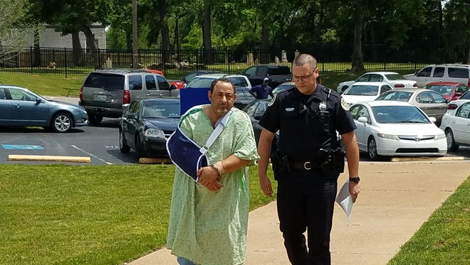 Nashville police officer Richard Olive escorts Michel Louka Guirguis, 52, into the police department the afternoon of Wednesday, May 17, 2017. Police said Guirguis would be charged in a domestic violence incident involving his wife and daughter on Tuesday at their home in Antioch.