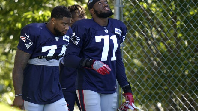 Patriots rookie linebackers Anfernee Jennings (left) and Josh Uche step on the field at the start of an NFL football training camp practice last Thursday, Aug. 20.