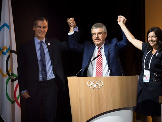 Eric Garcetti, Mayor of Los Angeles, left, International Olympic Committee, IOC, President Thomas Bach, from Germany, center, and Anne Hidalgo, Mayor of Paris, right, pose together during the International Olympic Committee (IOC) Extraordinary Session, at the SwissTech Convention Centre, in Lausanne, Switzerland, Tuesday, July 11, 2017. The IOC has decided it can pick both Los Angeles and Paris as Olympic host cities in September when the 2024 and 2028 Summer Games rights should be awarded simultaneously.  (Jean-Christophe Bott/Keystone via AP)