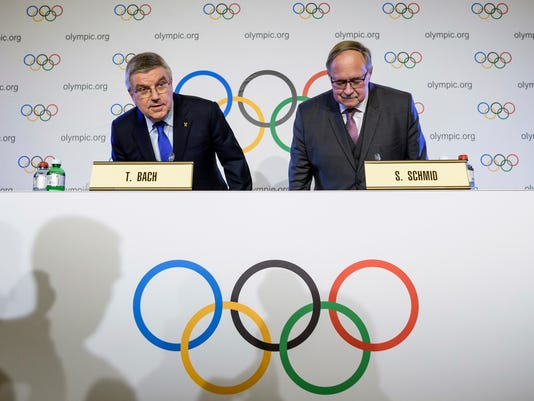 International Olympic Committee, IOC, President Thomas Bach from Germany, left, and Samuel Schmid, President of the IOC Inquiry Commission and former President of Switzerland, right, take their seats as they arrive for a press conference after an Executive Board meeting, in Lausanne, Switzerland, Tuesday, Dec. 5, 2017.  Russian athletes will be allowed to compete at the upcoming Pyeongchang Olympics as neutrals despite orchestrated doping at the 2014 Sochi Games, the International Olympic Committee said Tuesday. (Jean-Christophe Bott/Keystone via AP)
