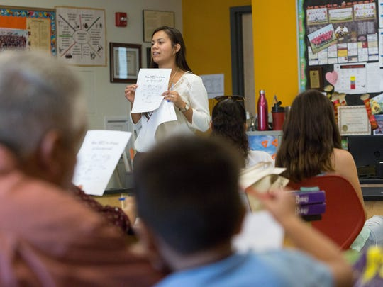 Erika Martinez, student advisor for the international welcome center at Centennial High School, talks with parents and students about the upcoming school year and what parents should expect from their children. Monday Aug. 28, 2017.