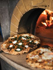 Wood-fired pizzas coming out of the oven at Dough Artisan
