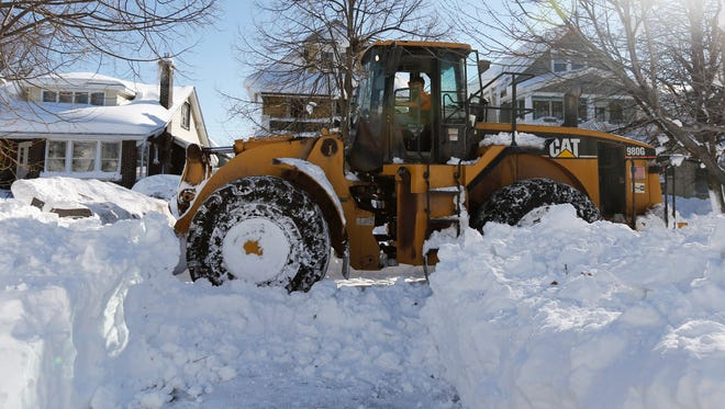 A front loader clears snow from a south Buffalo street on Friday. The epic snowfall that brought huge drifts and closed roads in the Buffalo area finally ended Friday, yet residents still couldn't breathe easy, as the looming threat of rain and higher temperatures through the weekend and beyond raised the possibility of floods and more roofs collapsing under the heavy loads.