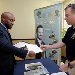 In this Feb. 6, 2015 photo, U.S. Marine Corps Veteran Arlington Robertson, of Fort Lauderdale, left, hands his resume to an Internal Revenue Service Special Agent, at the annual Veterans Career and Resource Fair in Miami.